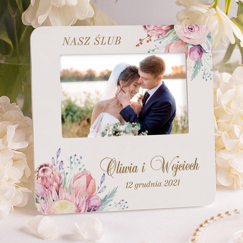 Ramka na zdjęcie ze ślubu prezent na ślub lub rocznicę. Na ramce znajdują się zdobienia wokół okienka na zdjęcie w postaci kwiatów, a także napisy: nasz ślub, imiona małżonków i data ślubu.
