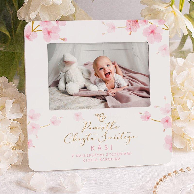 Ramka na fotografię dziecka w białym odcieniu. Idealny prezent dla maluszka na Chrzest Święty. Na ramce widnieje grafika przedstawiająca różowe kwiaty.