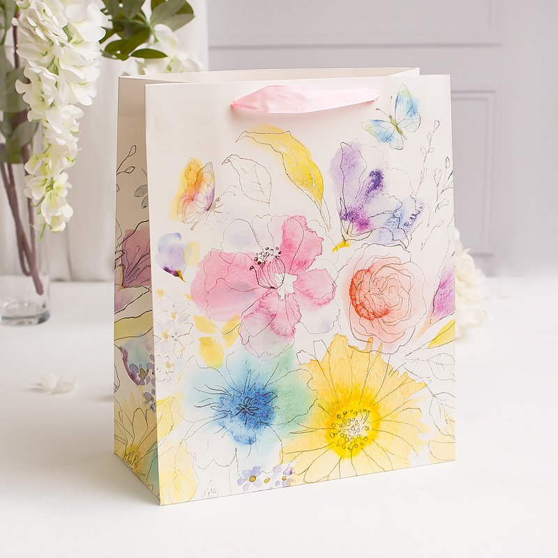Torebka papierowa w akwarelowe kwiaty, z uchwytami w formie różowych wstążek.