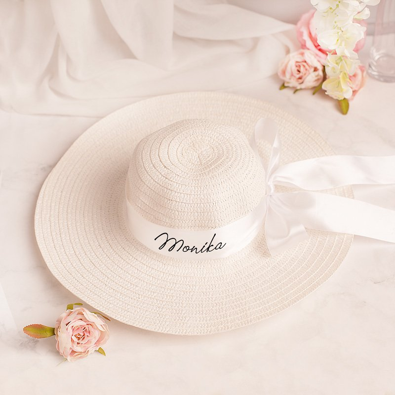 Pleciony kapelusz z imieniem jest w białym kolorze. Posiada dekoracyjną wstążkę z personalizacją.