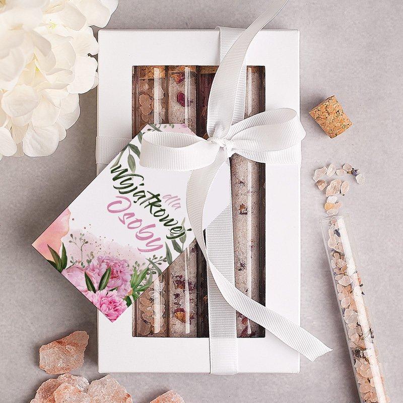 Kobiecy zestaw aromatyczny, pudełko z szklanymi fiolkami, w których znajduje się sól do kąpieli, płatki róż i muszelki. Pudełko przewiązane jest kokardą z bilecikiem.