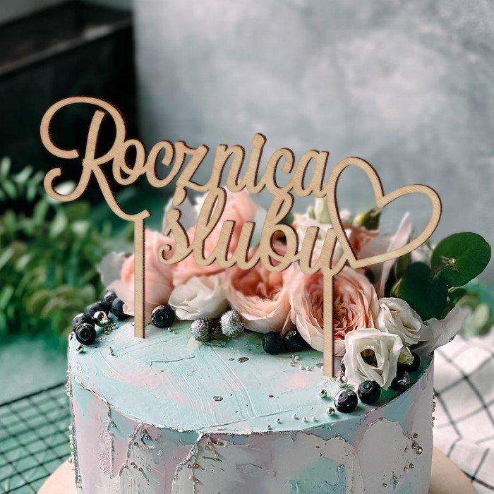 Topper rocznicowy na tort wykonany z jasnego drewna. Idealny dodatek na rocznicę ślubu. Na topperze widnieje urocze serduszko.