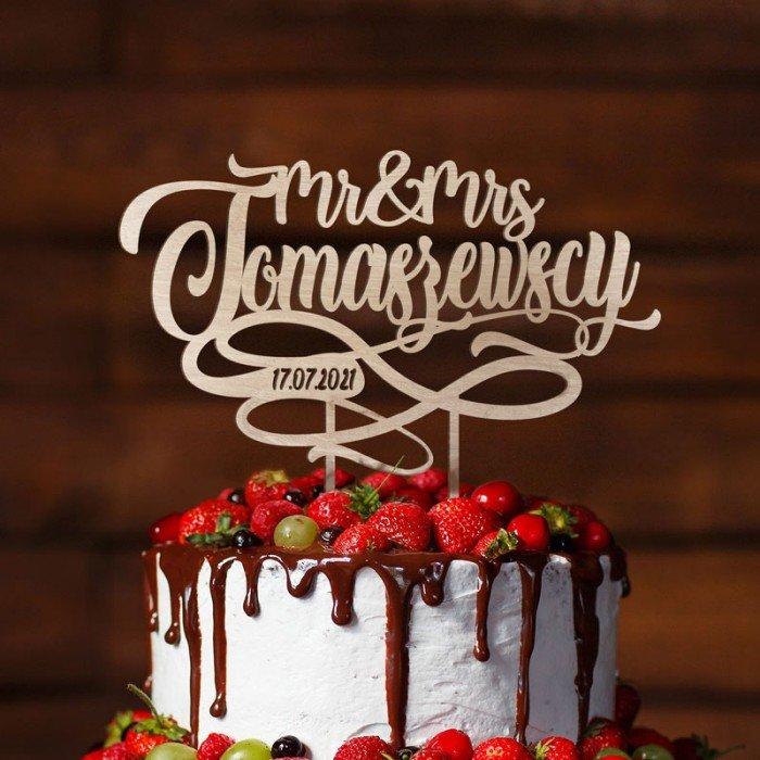 Personalizowany topper ślubny na tort wykonany z drewna, wzbogacony o nazwiska Pary Młodej.
