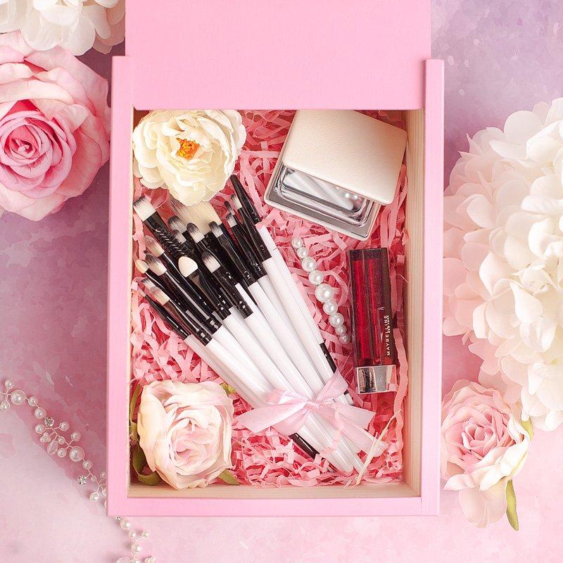 Zestaw prezentowy dla kobiety w różowej skrzynce. Wewnątrz znajdują się kobiece akcesoria do makijażu.