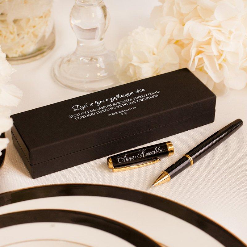 Długopisy w etui dla nauczyciela. Opakowanie jest w czarnym kolorze, na nim widnieją życzenia. Długopis posiada personalizację.